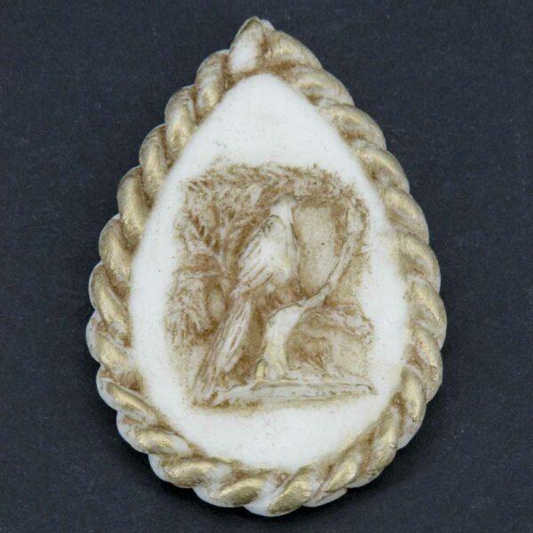 Medaillion in Tropfenform aus Wachs mit Vogelmotiv